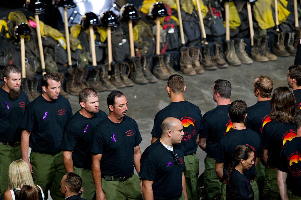 Description of . Former Granite Mountain Hotshot firefighters walk past ceremonial firefighter boots and clothing during a memorial service for the 19 fallen firefighters at Tim's Toyota Center in Prescott Valley, Ariz. on Tuesday, July 9, 2013.     (AP Photo/The Arizona Republic, Michael Chow, Pool)