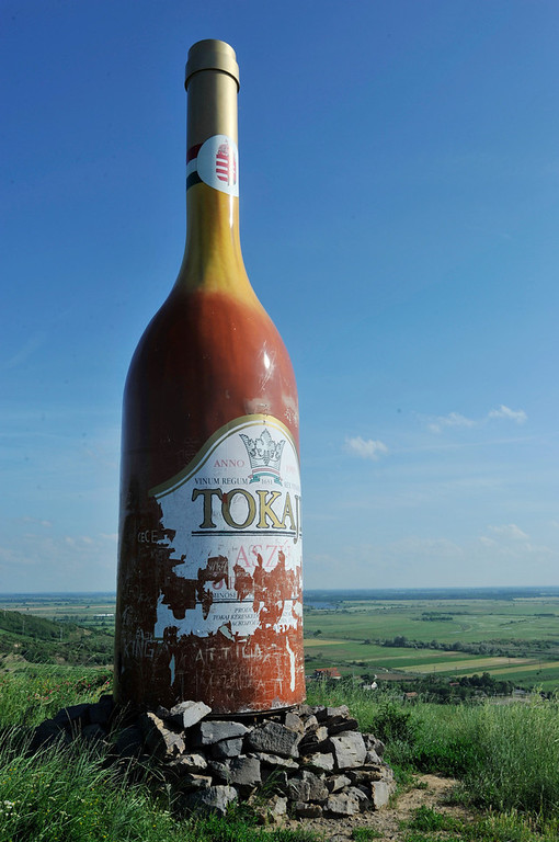 Description of . A motorcyclist passes an enormous mockup of a Tokaji aszu bottle of wine in the countryside in Tokaj, Hungary, on June 17, 2010. Traveling to the emerging Tokaj wine region can be a low-key experience where one can rub shoulders with working winemakers. (Chris Warde-Jones/The New York Times)