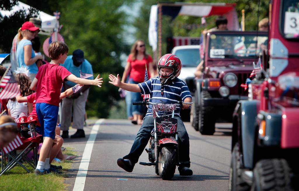 Description of . Patrick Ardis, 10, gets a high-five from his friend Porter Rosenberg, 10, left, while riding in the Cordova Independence Day Parade at the Cordova Community Center in Cordova, Tenn., on Thursday, July 4, 2013.  (AP Photo/The Commercial Appeal, Jim Weber)