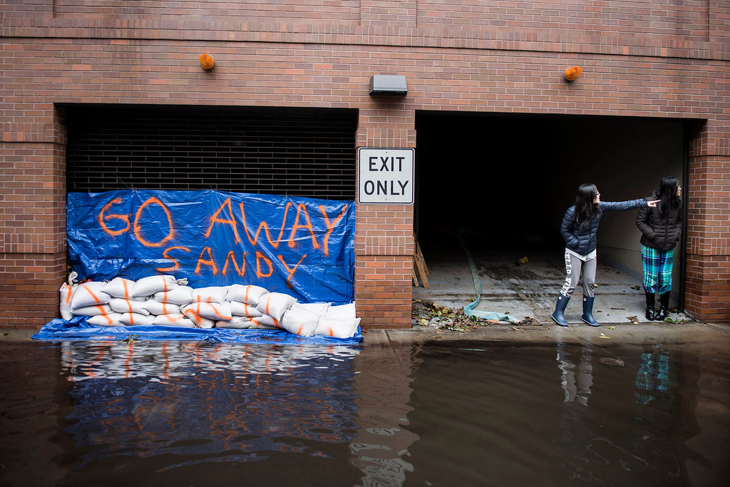 . People stand outside their apartment building October 31, 2012 in Hoboken, New Jersey.  Hurricane Sandy which made landfall along the New Jersey shore, has left parts of the state and the surrounding area flooded and without power.   AFP PHOTO/Brendan SMIALOWSKI