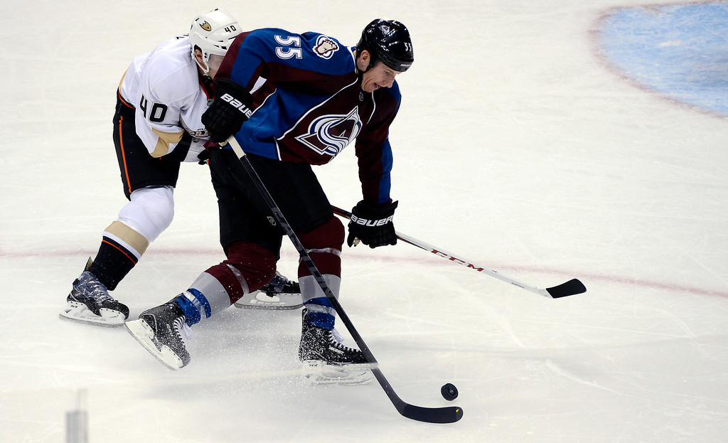 Description of . DENVER, CO. - FEBRUARY 06: Cody McLeod (55) of the Colorado Avalanche skates with the puck away from Jordan Hendry (40) of the Anaheim Ducks during the second period February 6, 2013 at Pepsi Center. The Colorado Avalanche take on the Anaheim Ducks during NHL action. (Photo By John Leyba / The Denver Post)