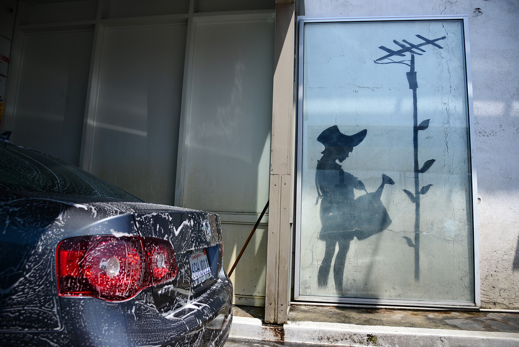 Description of . A gas station employee washes a car beside a piece of graffiti art believed to be by British street artist Banksy, in Los Angeles, California August 15, 2013. Another Banksy piece, titled