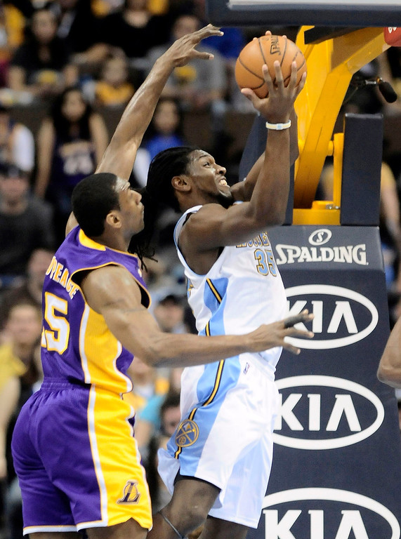 Description of . Denver Nuggets Kenneth Faried (R) slips past Los Angles Lakers Metta World Peace (L) for a shot during their NBA basketball game in Denver, Colorado February 25, 2013. REUTERS/Mark Leffingwell