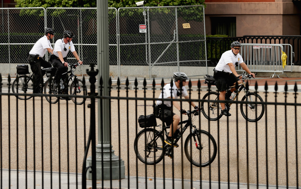 Description of . Members of the U.S. Secret Service Uniform Division ride bicycle patrols around the perimeter of the White House October 3, 2013 in Washington, DC. The executive mansion was put on lockdown after a report of shots fired at the U.S. Capitol.  (Photo by Chip Somodevilla/Getty Images)