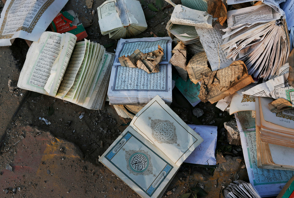 Description of . Copies of the Quran, Islam's holy book, some damaged, are pictured after they were salvaged from inside the Al Aqsa Martyrs mosque in Gaza City, destroyed by an overnight Israeli strike, on Tuesday, July 22, 2014. Diplomatic efforts intensified to end the two week war that has killed more hundreds of Palestinians and dozens of Israelis. (AP Photo/Lefteris Pitarakis)