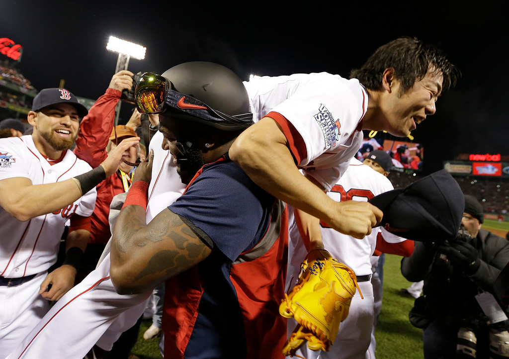 Description of . Boston Red Sox's David Ortiz lifts relief pitcher Koji Uehara after Boston defeated the St. Louis Cardinals in Game 6 of baseball's World Series Wednesday, Oct. 30, 2013, in Boston. The Red Sox won 6-1 to win the series. (AP Photo/David J. Phillip)