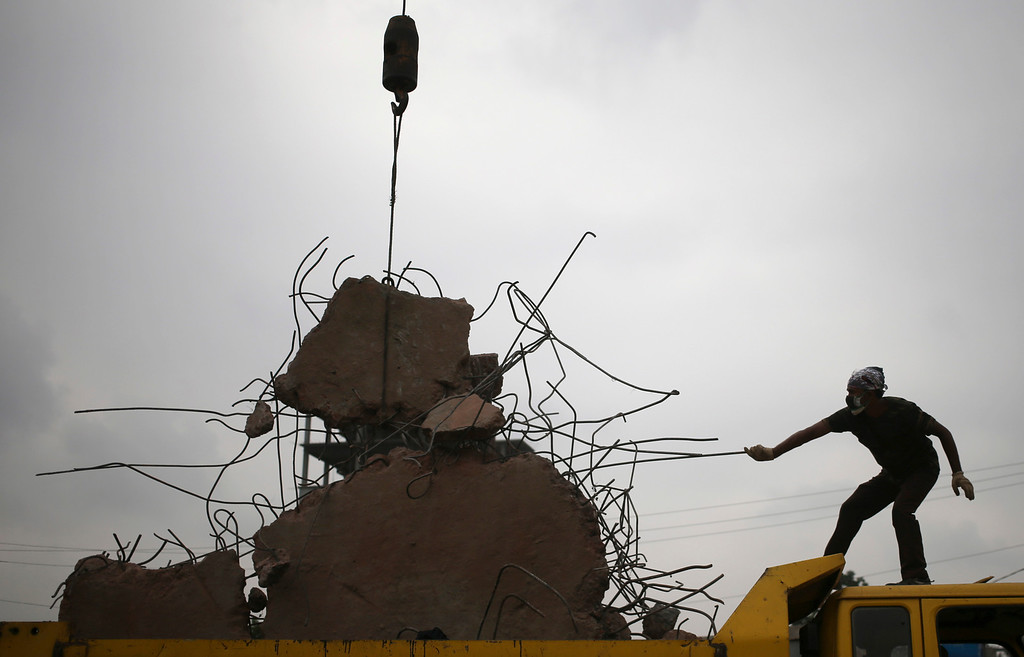 Description of . A worker leads a piece of debris into a dump truck at the site of a garment factory building collapse on Tuesday, April 30, 2013 in Savar, near Dhaka, Bangladesh.  (AP Photo/Wong Maye-E)