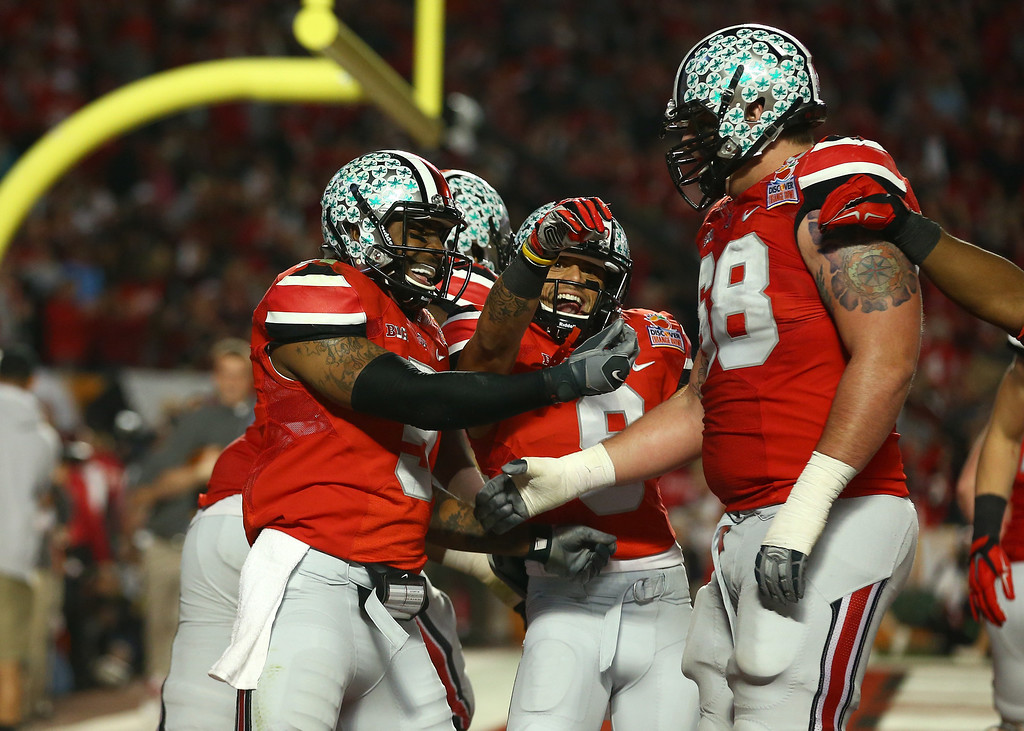 Description of . MIAMI GARDENS, FL - JANUARY 03: Braxton Miller #5, Devin Smith #9 and Taylor Decker #68 of the Ohio State Buckeyes celebrate after a touchdown by Miller in the second quarter against the Clemson Tigers during the Discover Orange Bowl at Sun Life Stadium on January 3, 2014 in Miami Gardens, Florida.  (Photo by Streeter Lecka/Getty Images)