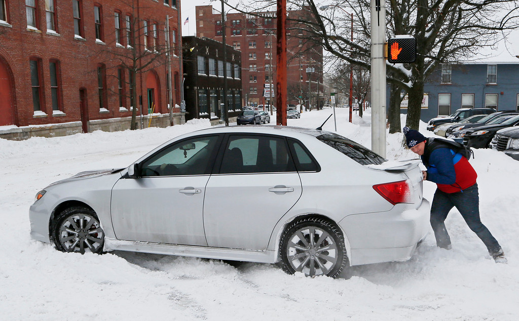 Description of . Aaron Madrid helps a motorist who became stuck in snow Wednesday, Feb. 5, 2014, at the intersection of Sixth and Ferry streets in Lafayette, Ind. Much of the state was blanketed by yet another round of heavy snow that began Tuesday afternoon and continued into the early morning hours of Wednesday. (AP Photo/Journal & Courier, John Terhune)
