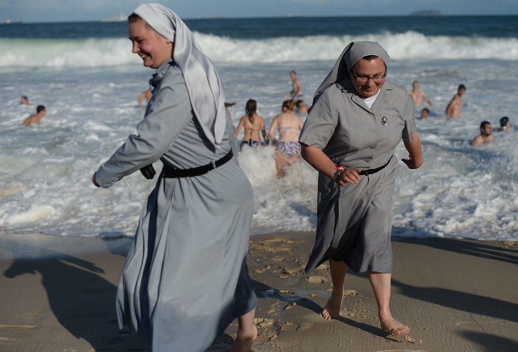 Description of . Two Polish nuns laugh on the shore as hundreds of thousands of young Catholic pilgrims attending World Youth Day (WYD) start gathering at Copacabana beach in Rio de Janeiro for a prayer vigil with Pope Francis, on July 27, 2013. In a speech to Brazil's political, religious and civil society leaders earlier, Pope Francis said a
