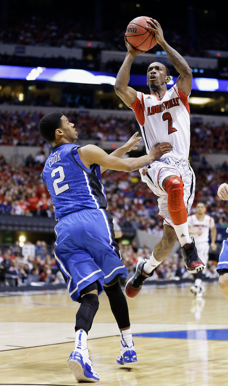 Description of . Louisville guard Russ Smith (2) goes up with a shot past Duke guard Quinn Cook (2) during the first half of the Midwest Regional final in the NCAA college basketball tournament, Sunday, March 31, 2013, in Indianapolis. (AP Photo/Michael Conroy)
