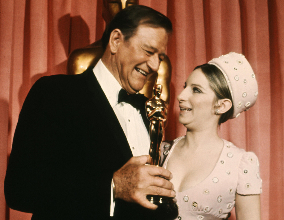 Description of . In this 1969 photo, US actor John Wayne accepts his Best Actor Oscar from US singer and actress Barbara Streisand. Wayne won for his role in