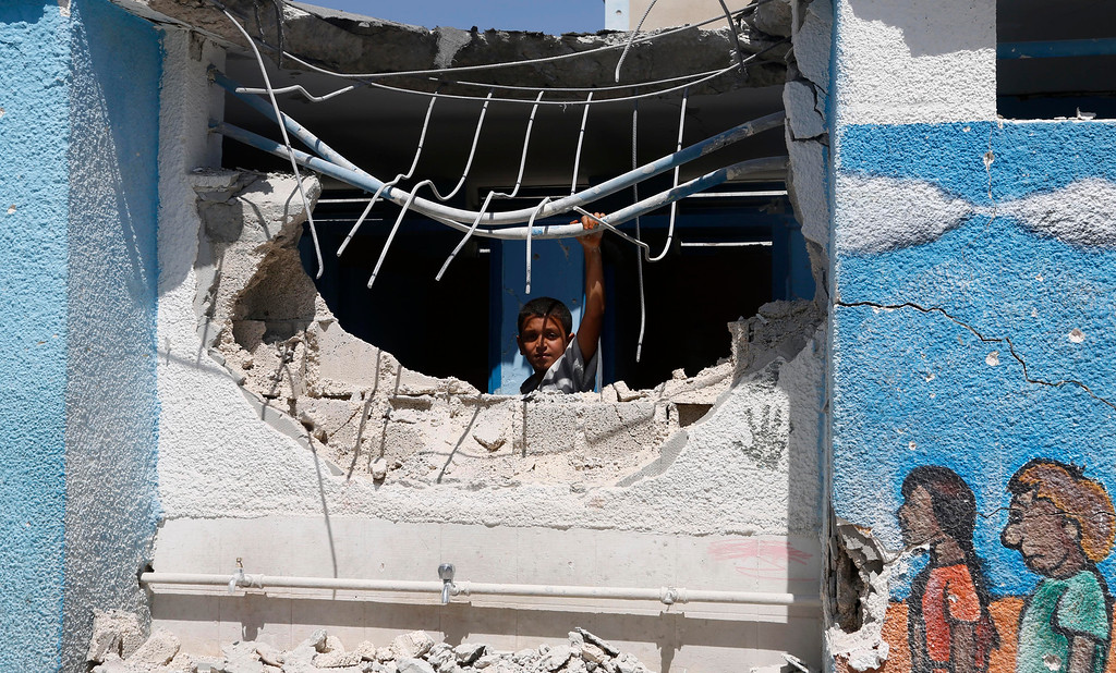Description of . A boy looks through the wall of a building damaged by an Israeli strike at the Abu Hussein U.N. school in the Jebaliya refugee camp in the northern Gaza Strip on Wednesday, July 30, 2014. Israeli tank shells slammed into a crowded U.N. school Wednesday sheltering Gazans displaced by fighting, killing more than a dozen and wounding tens after tearing through the walls of two classrooms, a spokesman for a U.N. aid agency and a health official said. The Israeli military said mortar shells had been fired from near the school, and that soldiers fired back. (AP Photo/Hatem Moussa)