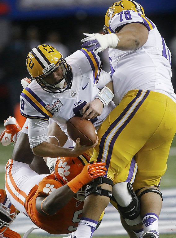. LSU quarterback Zach Mettenberger (8) is taken to the turf for a sack by Clemson defensive tackle Grady Jarrett (50) during the first half of the Chick-fil-A Bowl NCAA college football game, Monday, Dec. 31, 2012, in Atlanta. (AP Photo/John Bazemore)