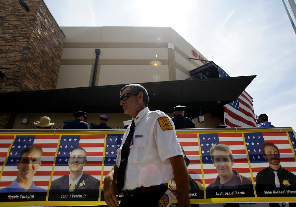 Description of . A firefighter walks past a banner showing some of the faces of the Prescott Fire Department's Granite Mountain Interagency Hot Shot Crew during a memorial in Prescott Valley, Arizona July 9, 2013. REUTERS/Joshua Lott