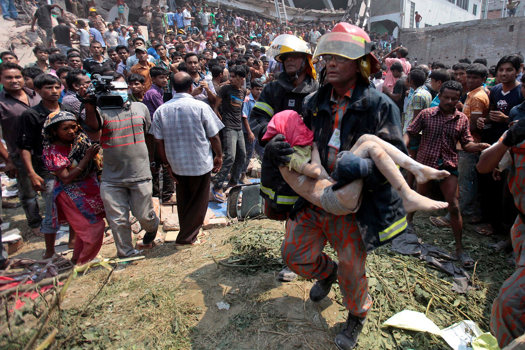 Description of . Rescue workers carry a young victim's body after an eight-story building housing several garment factories collapsed in Savar, near Dhaka, Bangladesh, Wednesday, April 24, 2013.  (AP Photo/ A.M. Ahad)