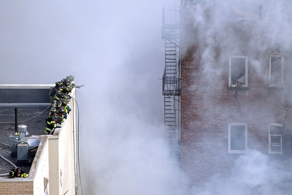 Description of . Firefighters from the Fire Department of New York (FDNY) respond to a five-alarm fire and building collapse at 1646 Park Ave in the Harlem neighborhood of Manhattan March 12, 2014 in New York City.  (Photo by Justin Heiman/Getty Images)