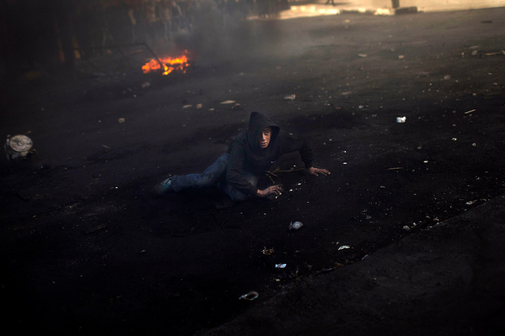 Description of . A Palestinian stone-thrower lays on the ground during clashes with Israeli forces in the West Bank city of Hebron, Thursday, April 4, 2013.  (AP Photo/Bernat Armangue, File)