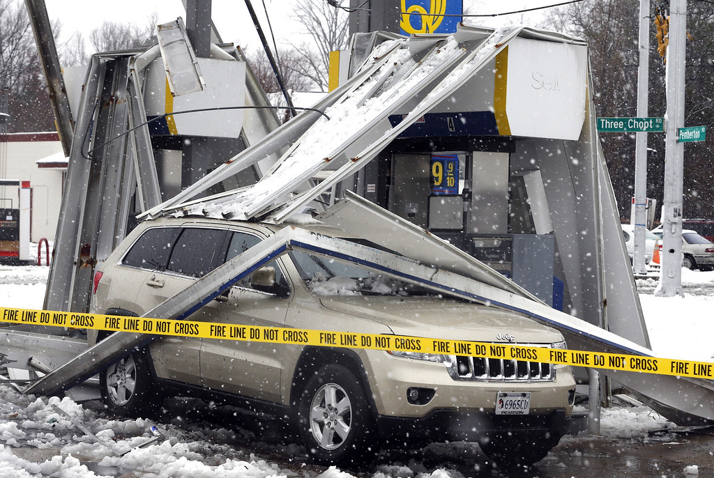 Description of . Gusting winds and a heavy wet snow combined to bring down the canopy over gas pumps at a station  in Henrico County, in suburban Richmond, Va. on Wednesday, March 6, 2013. The Richmond area dodged much of the late season storm while the western part of Virginia reporter up to 15 inches of snow. (AP PHOTO/ The Richmond Times-Dispatch, Joe Mahoney
