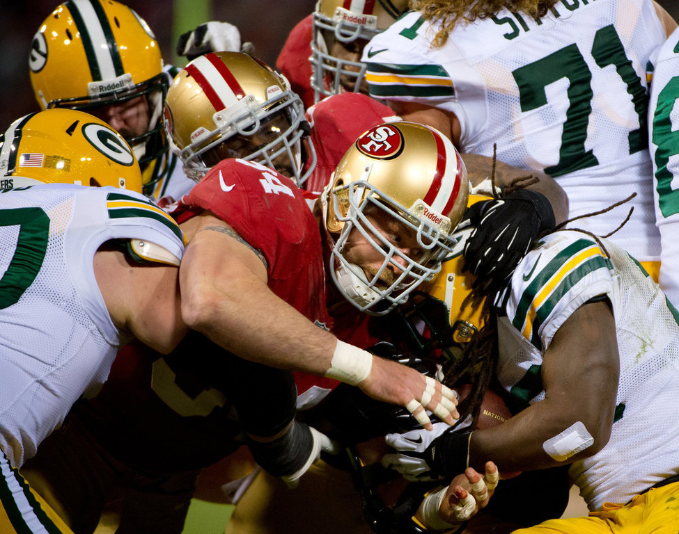 Description of . San Francisco 49ers Justin Smith stops Green Bay Packers DuJuan Harris in the second quarter of an NFC divisional playoff NFL football game on Saturday, Jan. 12, 2013, in San Francisco. (AP Photo/The Sacramento Bee, Jose Luis Villegas)