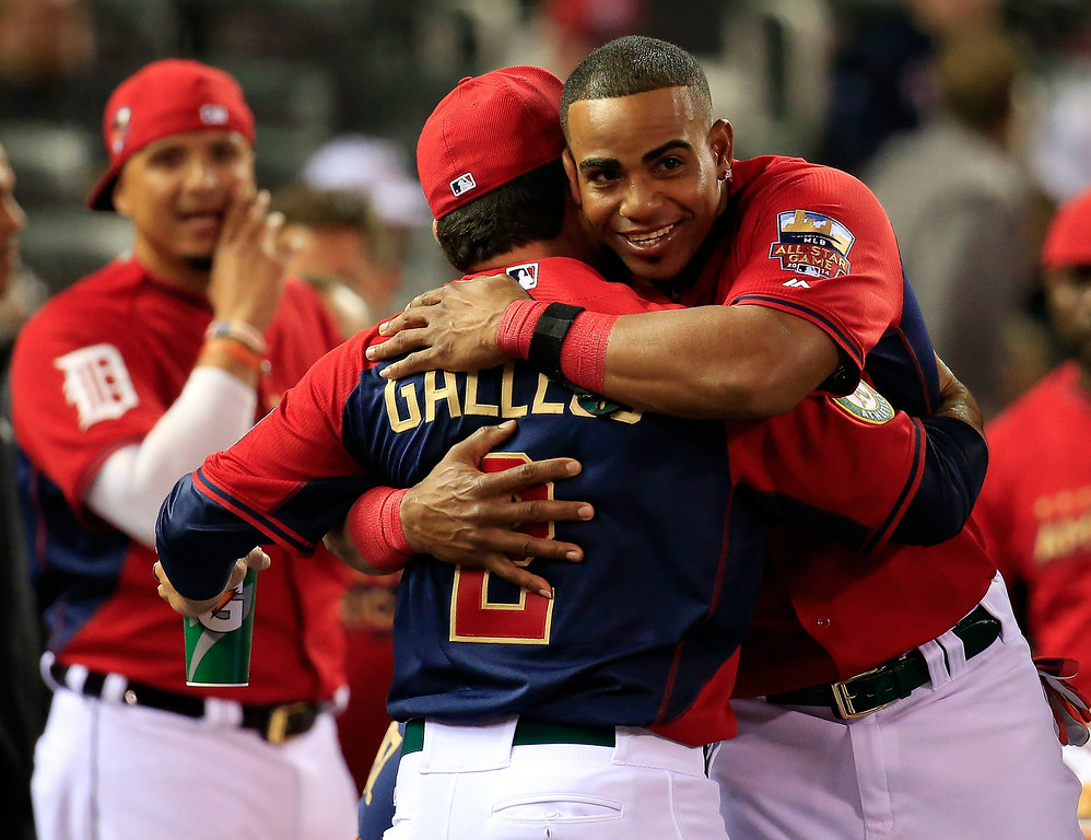 Description of . American League All-Star Yoenis Cespedes #52 of the Oakland A's celebrates with coach Mike Gallego, who threw to him in competition, after winning the Gillette Home Run Derby at Target Field on July 14, 2014 in Minneapolis, Minnesota.  (Photo by Rob Carr/Getty Images)