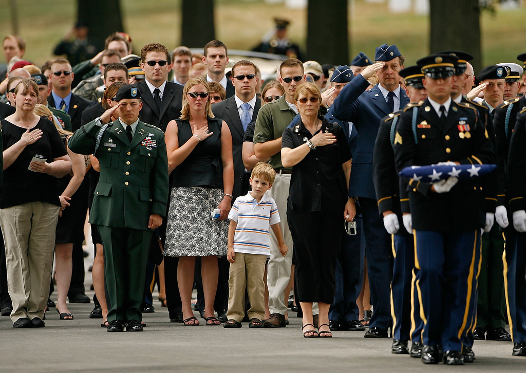 . Family, friends and fellow soldiers salute as US Army 1st Lt. Mark Harold Dooley remains are carried to the graveside during his funeral at Arlington National Cemetery July 13, 2007 in Arlington, Virginia.  A member of the Army National Guard\'s 3rd Battalion, 172nd Infantry Regiment (Mountain), 42nd Infantry Division, Dooley died in Ramadi, Iraq, when an improvised explosive device detonated near his vehicle during patrol operations on September 19, 2005.  (Photo by Chip Somodevilla/Getty Images)
