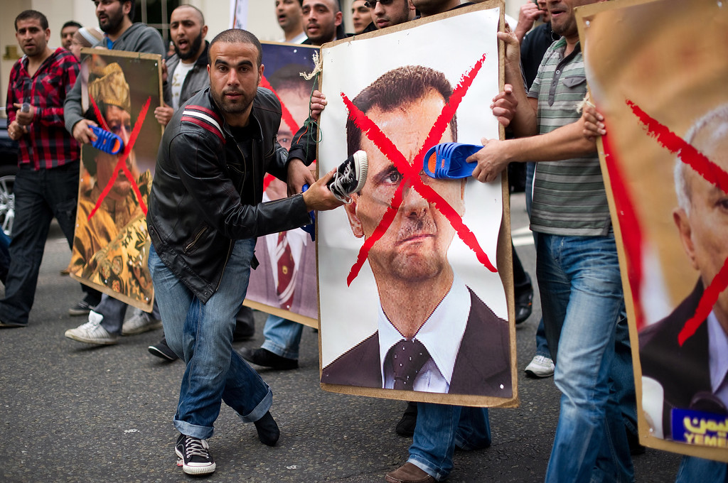 Description of . Protestors hit posters of Syria's President Bashar al-Assad (R) and Libyan leader Moamer Kadhafi  with shoes during a demonstration outside the Syrian embassy in London on May 7, 2011.  The demonstration was called to show support for the uprising in Libya, Syria, Bahrain and Yemen. LEON NEAL/AFP/Getty Images