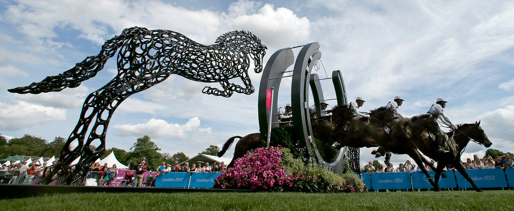 Description of . In this July 30, 2012 file photo and five frame multiple exposure, Andrew Hoy, of Australia, rides Rutherglen as he competes in the equestrian eventing cross-country stage at the 2012 Summer Olympics in London. (AP Photo/Charlie Riedel, File)