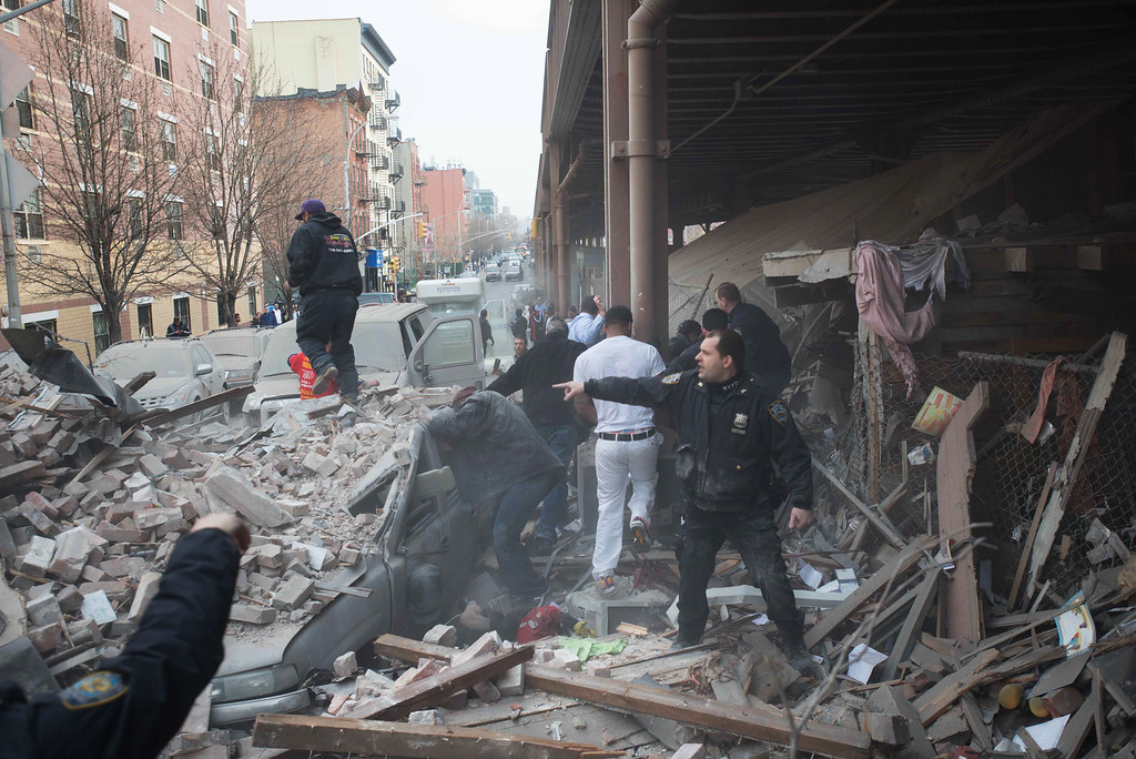 Description of . Police respond to the scene of an explosion that leveled two apartment buildings in the East Harlem neighborhood of New York, Wednesday, March 12, 2014.  (AP Photo/Jeremy Sailing)