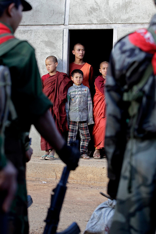 Description of . Buddhist novices and a boy look out from a monestary while  soldiers from Ta-ang National Liberation Army (TNLA), one of the ethnic rebel groups, prepare in Homain village, Nansam Township, Northern Shan State, Myanmar on Jan. 13, 2014. EPA/NYEIN CHAN NAING