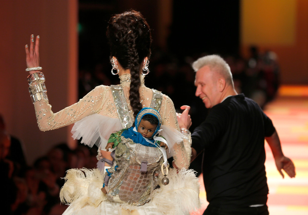 Description of . French fashion fashion designer Jean-Paul Gaultier walks with the model wearing the wedding gown as part of his Spring-Summer 2013 Haute Couture fashion collection, presented in Paris, Wednesday, Jan.23, 2013. (AP Photo/Jacques Brinon)
