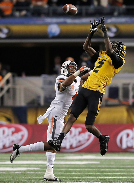 Description of . Missouri wide receiver L'Damian Washington (2) makes a reception over Oklahoma State cornerback Justin Gilbert (4) during the second half of the Cotton Bowl NCAA college football game, Friday, Jan. 3, 2014, in Arlington, Texas.  (AP Photo/Brandon Wade)