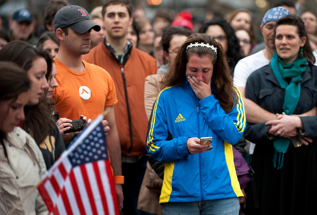 """Description of . A woman, wearing a Boston Marathon 2013 jacket, cries as people gather in the Boston Commons for a vigil on April 16, 2013 in Boston, in the aftermath of two explosions that struck near the finish line of the Boston Marathon on April 15. Investigators said the range of suspects and motives in the grisly Boston bombings remained \""""wide open\"""" as experts assessed remnants of the crude devices designed to inflict maximum suffering.   DON EMMERT/AFP/Getty Images"""