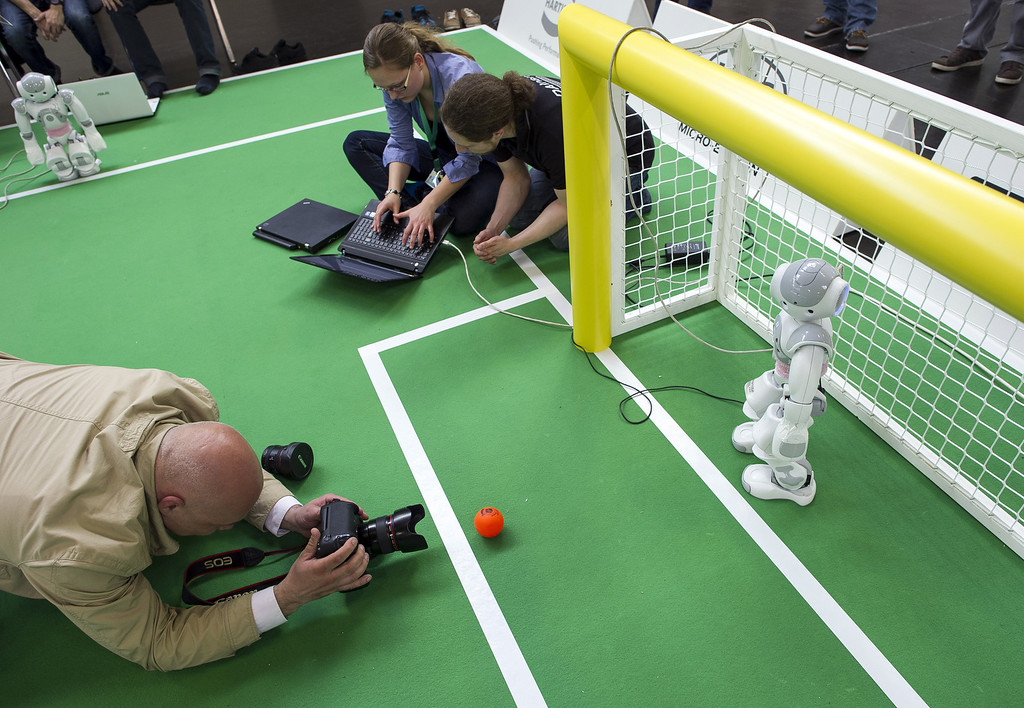 Description of . MAGDEBURG, GERMANY - APRIL 26:  A Photographer takes a picture at the 2013 RoboCup German Open tournament on April 26, 2013 in Magdeburg, Germany. The robots, which are a model called Nao, manufactured by Aldebaran Robotics, perform autonomously and communicate with one another via WLAN. The three-day tournament is hosting 43 international teams and 158 German junior teams that compete in a variety of disciplines, including soccer, rescue and dance.  (Photo by Jens Schlueter/Getty Images)