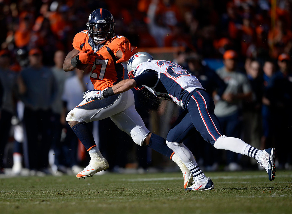 Description of . Denver Broncos running back Knowshon Moreno (27) fights off a tackle by New England Patriots strong safety Steve Gregory (28) and gets a first down in the second quarter to set up a Broncos touchdown. The Denver Broncos take on the New England Patriots in the AFC Championship game at Sports Authority Field at Mile High in Denver on January 19, 2014. (Photo by AAron Ontiveroz/The Denver Post)