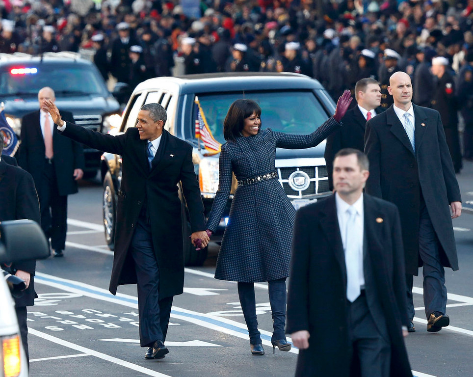 Description of . U.S. President Barack Obama and first lady Michelle Obama walk down Constitution Avenue after emerging from the presidential limousine during the inaugural parade from the Capitol to the White House in Washington, January 21, 2013.   REUTERS/Jason Reed