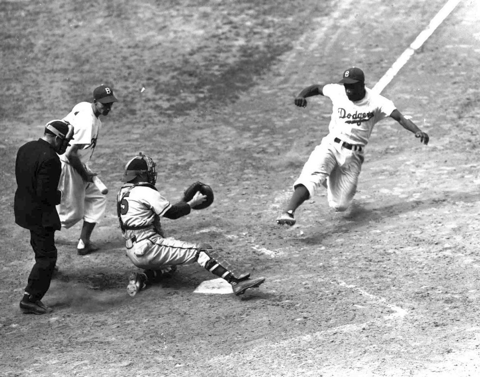 Description of . Brooklyn Dodgers Jackie Robinson steals home as part of a triple steal in the Boston Braves-Booklyn Dodgers game at Brooklyn\'s Ebbets Field in August 1948. Robinson broke the color barrier and changed baseball forever.  (AP Photo/files)