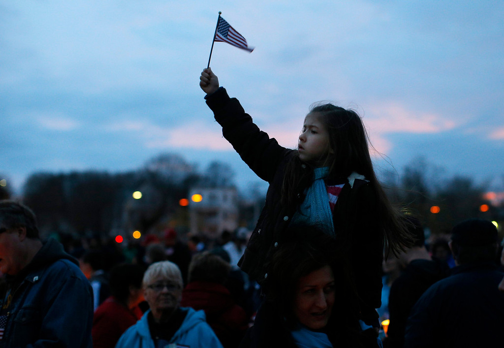 Description of . A girl holds up a U.S. flag during a candlelight vigil in the Dorchester neighborhood of Boston, Massachusetts April 16, 2013 where eight-year-old Boston Marathon bombing victim Martin Richard lived. A Little League baseball player, Martin lived in the blue Victorian house in working-class Dorchester - a Boston neighborhood dotted with