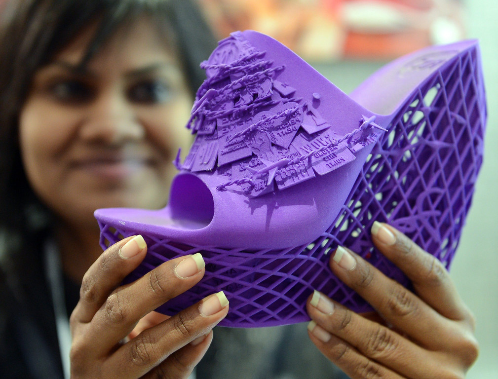 Description of . A stand assistant holds a shoe printed with a 3D printer at the Consumer Electronics Show (CES) 2014 in Las Vegas, USA, 08 January 2014. The fair runs from 07 to 10 January 2014. This new way of printing objects can create anything from guns to doorknobs to replacement parts for a dishwasher. The technology is getting closer to mass market appeal as it becomes cheaper. Reports state online retailers are eying a world where people shop on the internet and then print out their purchases at home.  EPA/BRITTA PEDERSEN