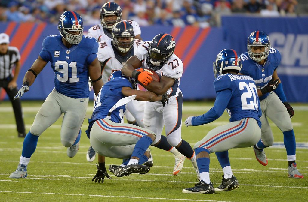 Description of . Denver Broncos running back Knowshon Moreno (27) runs over New York Giants free safety Ryan Mundy (21) for a big gain during the fourth quarter September 15, 2013 MetLife Stadium. (Photo by John Leyba/The Denver Post)