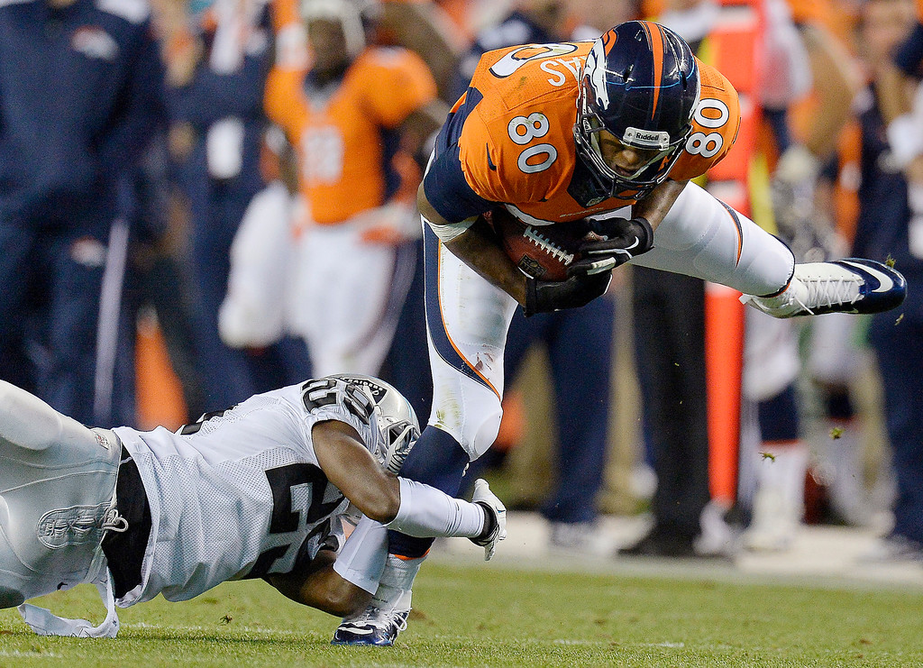 Description of . Denver Broncos tight end Julius Thomas (80) eludes a tackle by Oakland Raiders cornerback Brandian Ross (29) in the first quarter in Denver.   (Photo by John Leyba/The Denver Post)