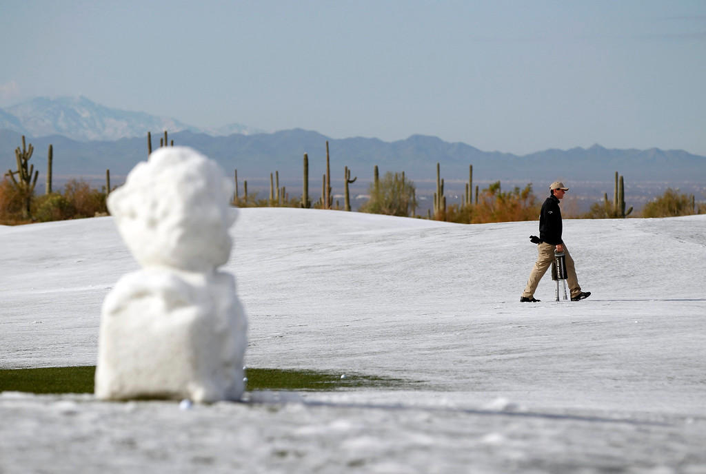 Description of . A course worker picks up golf balls on the driving range as snow and ice continues to delay first round play of the WGC-Accenture Match Play Championship golf tournament in Marana, Arizona February 21, 2013. REUTERS/Matt Sullivan