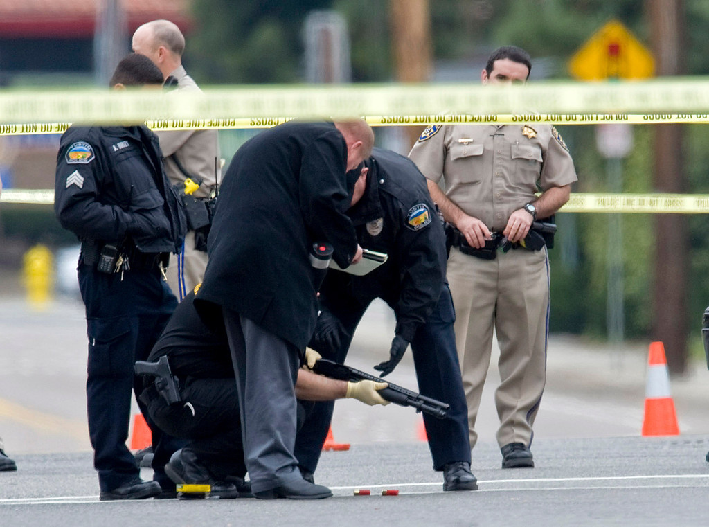 . Police investigators examine a gun laying in the street at the intersection of Wanda Road and Katella Avenue in Orange, Calif., early Tuesday, Feb. 19, 2013 near where a body laid moments before. (AP Photo/The Orange County Register, Mark Rightmire)