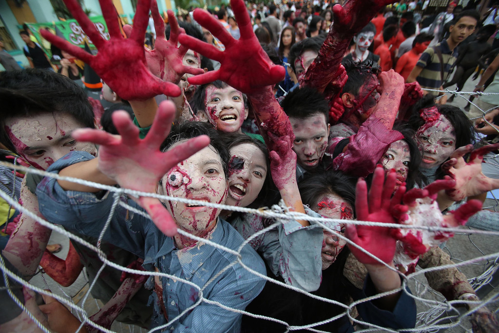 Description of . Filipinos wearing zombie costumes act during  a Halloween Parade in Marikina city, east of Manila, Philippines on Wednesday, Oct. 30, 2013. Hundreds of residents and government employees joined the parade as the country prepares to observe All Saints Day on Nov. 1. (AP Photo/Aaron Favila)