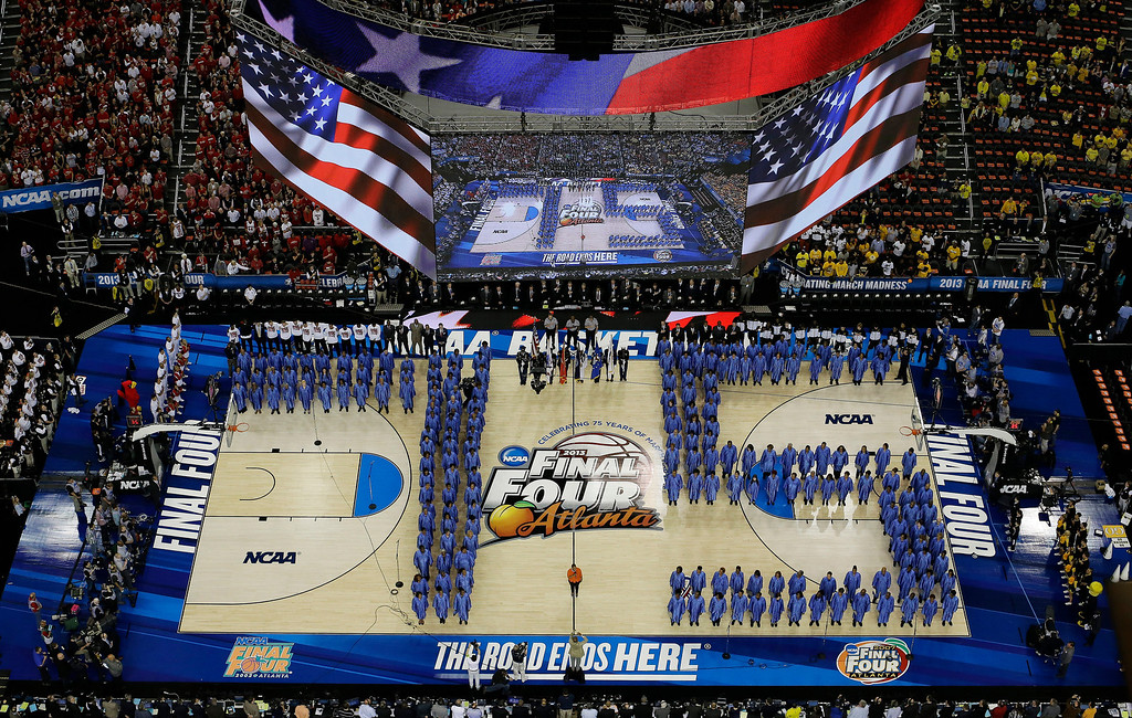 Description of . The National Anthem is performed as a chorus forms a 75 for the 75th anniversary of the Final Four before the first half of the NCAA Final Four tournament college basketball semifinal game between Louisville and Wichita State Saturday, April 6, 2013, in Atlanta. (AP Photo/David J. Phillip)