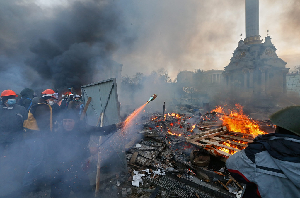 Description of . Protesters launch a rocket as they clash with riot police during on-going anti-government protests in downtown Kiev, Ukraine, 19 February 2014.  EPA/SERGEY DOLZHENKO