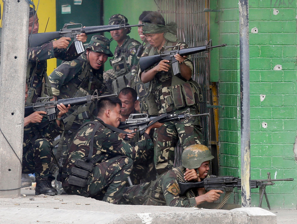 Description of . Government troopers fire their weapons as they continue their assault on Muslim rebels Thursday, Sept. 12, 2013, in Zamboanga city in the southern Philippines.  (AP Photo/Bullit Marquez)