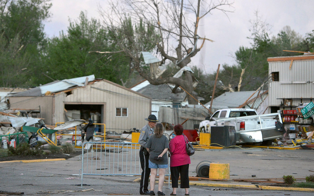 Description of . A officer talks to people at 15th and Military following Sunday's tornado in Baxter Springs, Kan., Sunday April 27, 2014.  A powerful storm system rumbled through the central and southern United States on Sunday, spawning a massive tornado that  carved through Little Rock's northern suburbs and another that hit Oklahoma and Kansas. (AP Photo/The Joplin Globe, Roger Nomer )