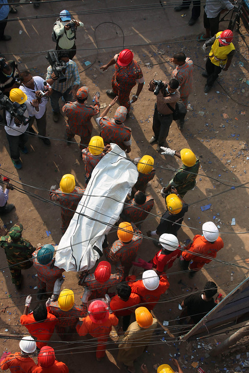 Description of . In this photograph taken  on April 29, 2013, Bangladeshi firefighters carry the body of garment worker Shahina Akter following her unsuccessful rescue from the eight-story building that collapsed in Savar, on the outskirts of Dhaka.  Bangladesh widow Shahina Akter's vain 100-hour struggle to survive the collapse last week of a garment factory has made her the tragic face of the nation's worst industrial disaster. AFP PHOTO/STR/FILESSTRDEL/AFP/Getty Images