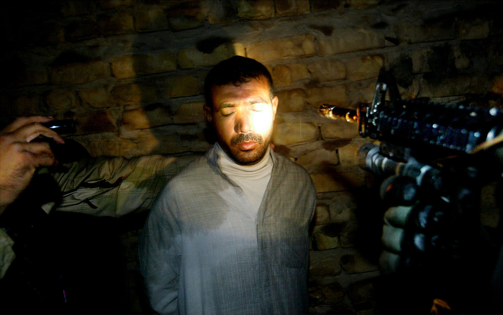 ". U.S. paratroopers with the 1-504th regiment of the 82nd Airborne Division from Ft. Bragg, North Carolina, nicknamed the ""Red Devils,\"" shine lights onto the face of a detained man while they try to identify him during a raid November 26, 2003 in Nassar el al Salaam, Iraq. The man was questioned and later released. The overnight raid netted two men suspected of militant activities against American forces.   (Photo by Chris Hondros/Getty Images)"